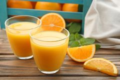 Glasses of tasty orange juice and box with fruit Royalty Free Stock Photo