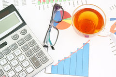 Glasses, tea and calculator on paper table Royalty Free Stock Photos