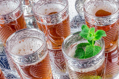 Glasses of tea with mint sprig. Ornate Moroccan tea glasses with mint sprig on silver tray Royalty Free Stock Images