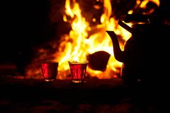 Glasses with tea near the fire with flaming wood at night.  Royalty Free Stock Images