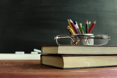 Glasses teacher books and a stand with pencils on the table, on the background of a blackboard with chalk. The concept of the teac