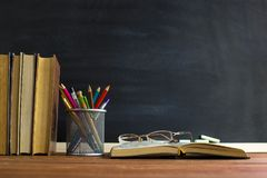 Glasses teacher books and a stand with pencils on the table, on the background of a blackboard with chalk. The concept of the teac stock photography