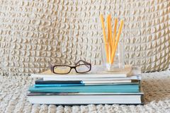 Glasses teacher books and a stand with pencils on the table. The concept of the teacher`s day. Copy space royalty free stock photography