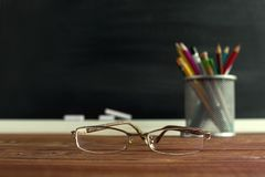 Glasses teacher and a stand with pencils on the table, on the background of a blackboard with chalk. The concept of the teacher`s