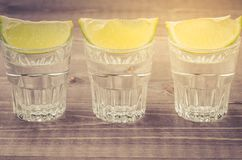 Glasses of tequila with a lime stand in a row/glasses of tequila. With a lime stand in a row on a wooden background royalty free stock photography