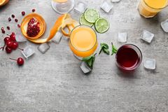 Glasses of Tequila Sunrise cocktail and ingredients. On grey background Stock Image