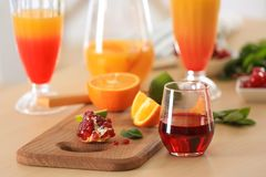 Glasses of Tequila Sunrise cocktail with ingredients. On kitchen table Stock Images