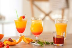 Glasses of Tequila Sunrise cocktail with ingredients. On table Royalty Free Stock Images