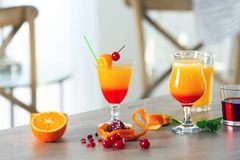 Glasses of Tequila Sunrise cocktail with ingredients. On table Royalty Free Stock Photo