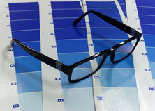 Glasses on a test cyan print Royalty Free Stock Image