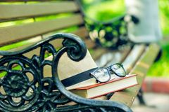 Glasses on a thick book and a straw hat forgotten. On a park bench Stock Photography