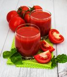 Glasses with tomato juice. And fresh tomatoes on a table Stock Images
