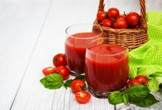 Glasses with tomato juice. And fresh tomatoes on a table Royalty Free Stock Photography