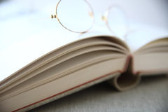 Glasses on top of book Stock Photos