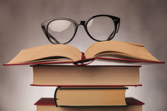 Glasses on top of a pile of books. Pair of glasses on top of a pile of books , shot in studio Stock Images