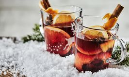 Glasses of traditional spicy Christmas Gluhwein. Two glasses of traditional spicy Christmas mulled hot Gluhwein with orange, cinnamon and star anise on fresh Royalty Free Stock Photography