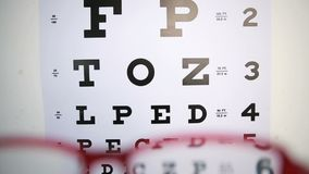 Glasses trying to focus on reading test Royalty Free Stock Photos