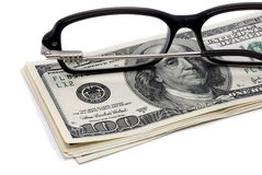 Glasses and US hundred dollar bills over white. Royalty Free Stock Photos
