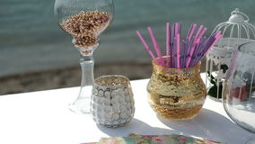 Glasses and vases on table by sand seashore. stock video footage