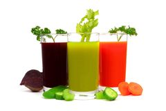Glasses of vegetable juice in a group with ingredients, isolated. Three glasses of vegetable juice, beet, greens and carrot in a group with ingredients, isolated Stock Images