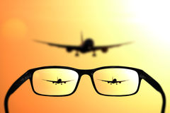 Glasses, vision concept, plane. Glasses and landing passenger jet plane - great for topics like vision, plane traveling or eyesight problems Royalty Free Stock Image