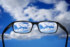 Glasses, vision concept, sky. Glasses and clear sky with clouds - great for topics like vision or eyesight problems Stock Image