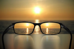 Glasses, vision concept, sunset. Glasses and ocean/sunset sky - great for topics like vision, eyesight problems or holiday Stock Images