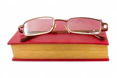 Glasses for vision lie in the book Stock Photography