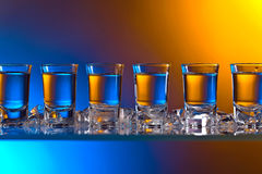 Glasses of vodka . Glasses of vodka with ice on a glass table in bar Royalty Free Stock Photography