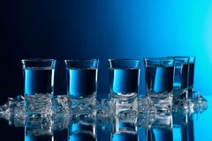 Glasses of vodka with ice on a glass table royalty free stock image