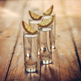 Glasses of vodka with lemon on wooden background. Toning image. Royalty Free Stock Image