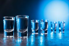 Glasses of Vodka lit with blue backlight stock photography