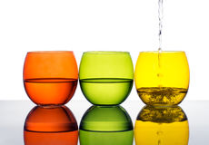Glasses of water or dink, yellow, green, orange colours. Stock Images