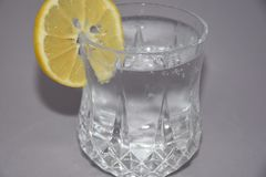 A cold water glass with lemon  on white. Glasses water drink lemon cold ice  liquid white transparent beverage clear alcohol clean blue food fresh cool healthy Royalty Free Stock Photography