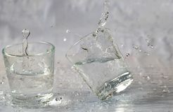 Glasses of water falling and jumping with splashes and drops.  stock photos