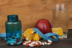 Glasses of water and fruit. Supplements and vitamins for the diet program. Food for weight reduction Royalty Free Stock Photos