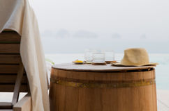 Glasses of water with hat on barrel at hotel beach Stock Photos