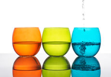 Glasses of water, yellow green, orange, turquoise colours. White Stock Image