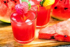 Watermelon slices and juice on wooden table. Glasses with watermelon juice and ice and sliced fresh ripe watermelon. Delicious summer diert concept. Selective Stock Photos