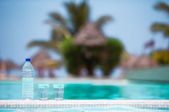 Glasses of waters and bottle background swiming pool Stock Photos