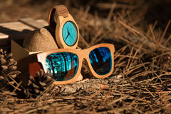 Glasses and wathes in the woods. Wooden wathes and glasses with blue face and lens royalty free stock photo