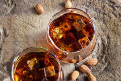Glasses whiskey bourbon with ices in glass and almonds on old wooden Royalty Free Stock Images