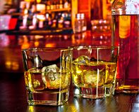 Glasses of whiskey with ice on bar table near whiskey bottle on warm atmosphere Stock Image