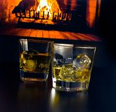 Glasses of whiskey with ice cubes in front of the fireplace Stock Image