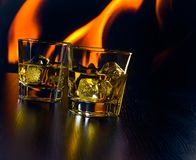 Glasses of whiskey with ice cubes in front of the flame Stock Images