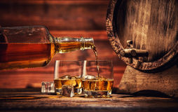 Glasses of whiskey with ice cubes served on wood. Pouring whiskey from bottle to two glasses with ice cubes, served on wooden planks. Vintage countertop with keg Royalty Free Stock Images