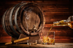 Glasses of whiskey with ice cubes served on wood. Pouring whiskey from bottle to two glasses with ice cubes, served on wooden planks. Vintage countertop with keg Royalty Free Stock Photos