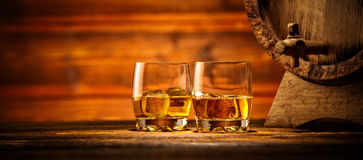 Glasses of whiskey with ice cubes served on wood. Two glasses of whiskey with ice cubes served on wooden planks with keg. Vintage countertop with highlight and a Stock Images