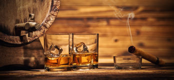 Glasses of whiskey with ice cubes served on wood. Two glasses of whiskey with ice cubes served on wooden planks with keg. Vintage countertop with highlight and Royalty Free Stock Photography