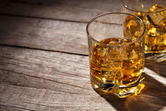 Glasses of whiskey with ice on wood Stock Photos